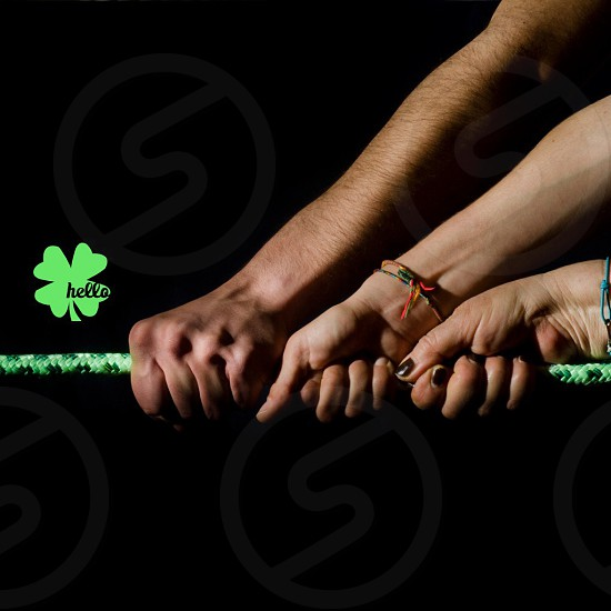 Human hands pulling a green wrope photo