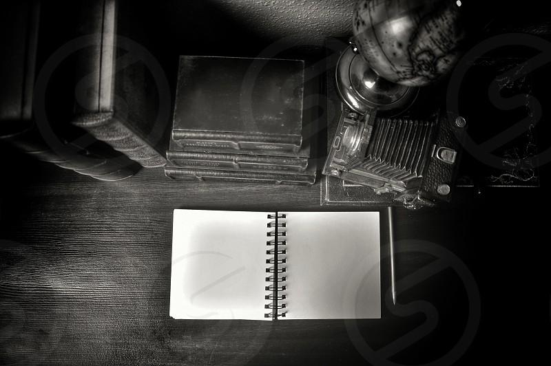 white spiral note book beside black engine photo