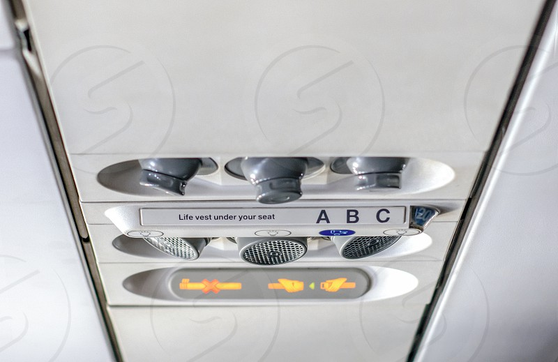 control panel to regulate the direction of personal lights air conditioning with the indication of smoking ban and to keep the safety belts fastened inside a flight cabin of an airplane photo