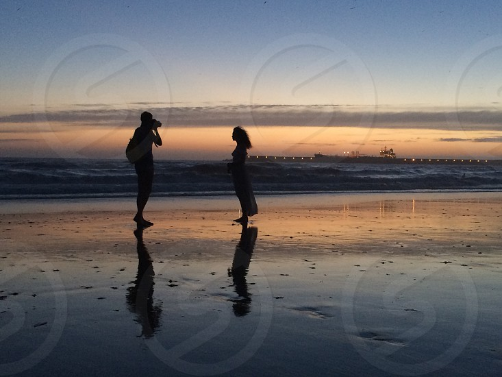 man and woman standing on beach in front of sunset photo