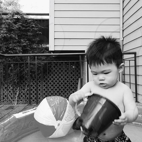 baby holding black plastic bucket photo