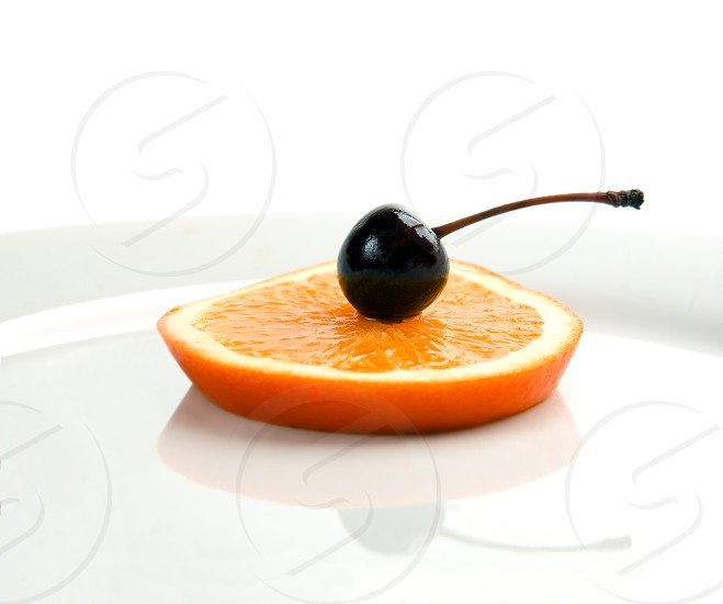 slice of orange with cherry on top isolated on a plate with reflection photo
