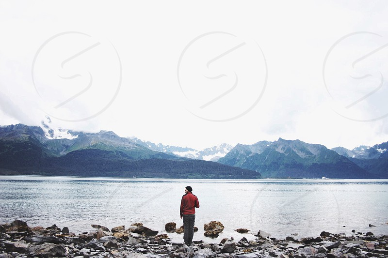 person in red jacket standing on seashore during daytime photo