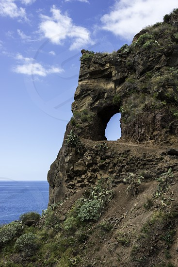 rock on the eastcoast of madeira near Calheta with hola and view to the blue sky photo