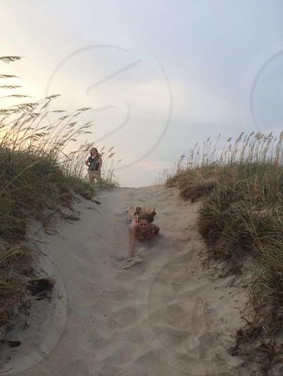 woman sliding on sand photo