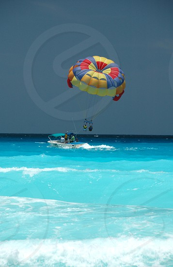 2 people in white speedboat beside yellow blue red parachute over blue water photo