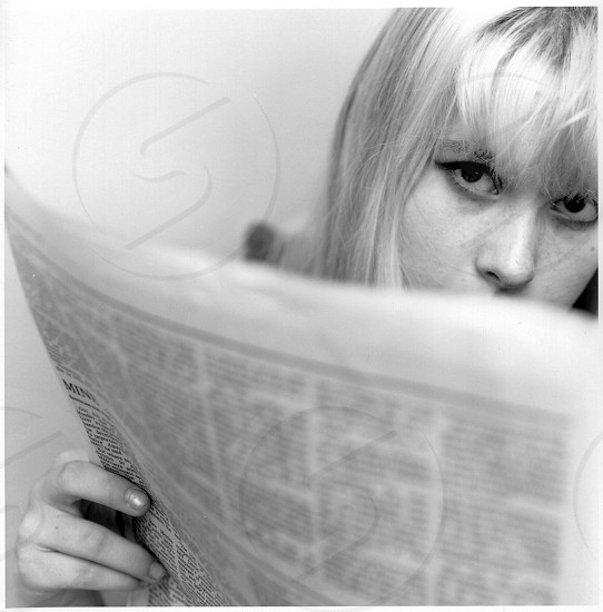 woman reading the newspaper grayscale photography  photo