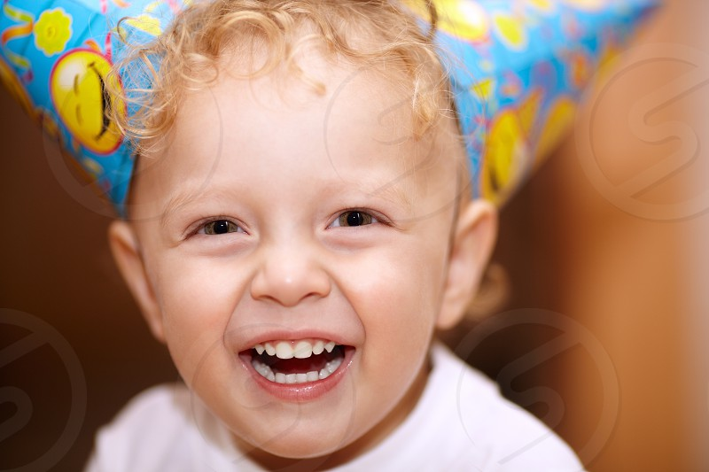 Closeup facial portrait of a happy laughing little boy with wavy blond hair looking directly into the camera photo