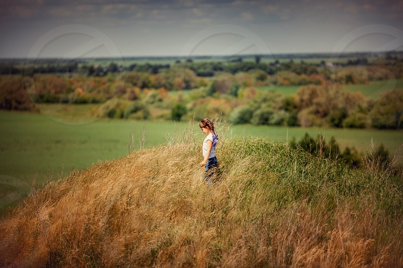 Little girl on the hill with summer grass  photo