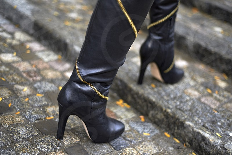 Close up of female wearing luxury designer high heel leather boots on cobblestone steps in Zurich city centre photo