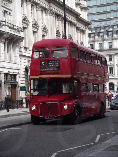 red 2-storey bus on road beside white concrete high-rise building photography photo