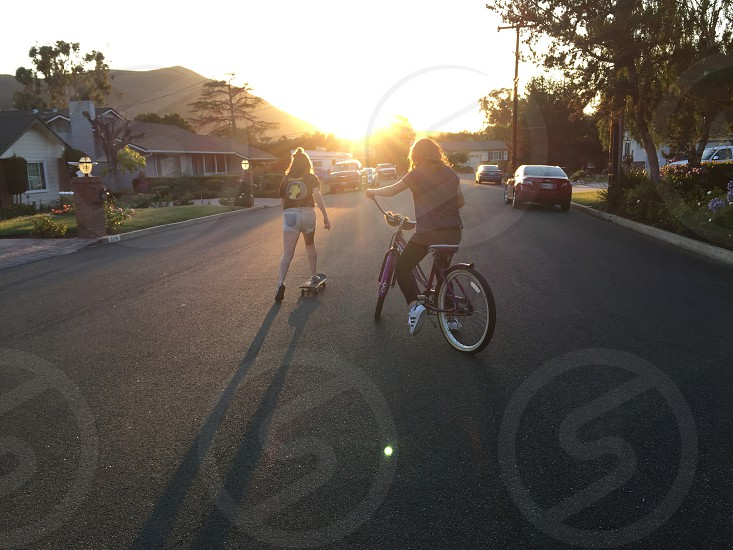 woman riding beach cruiser in front of woman riding skateboard photo