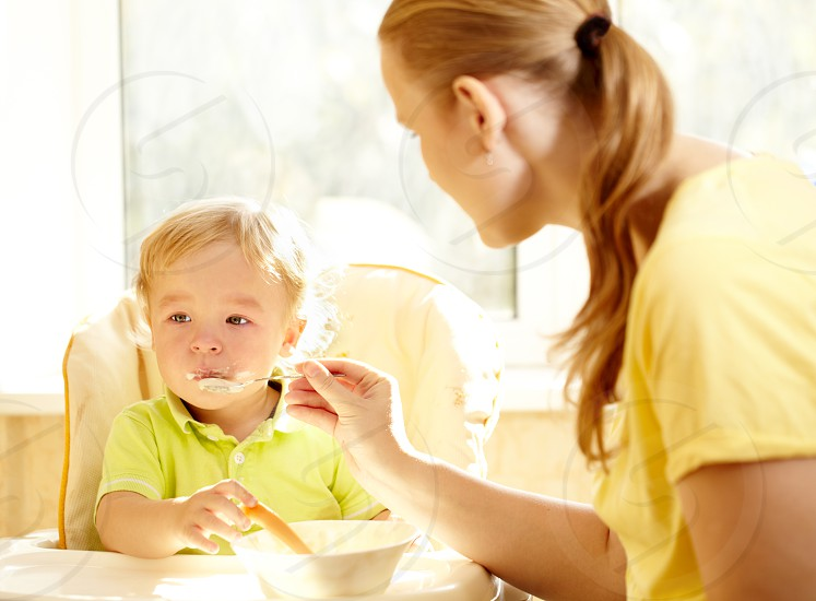 Young mother is feeding her two year old boy with porridge. photo