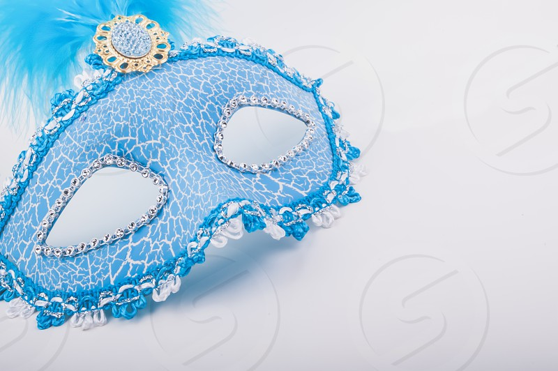 Studio shot with a traditional italian carnival mask in blu white background. photo