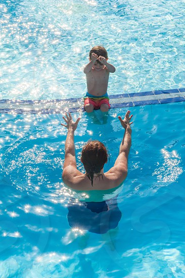 Child with mum in a swimming pool encouraged to take a dive into water. photo