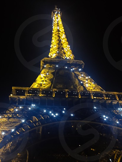 eiffel tower at night with white and yellow lights photo