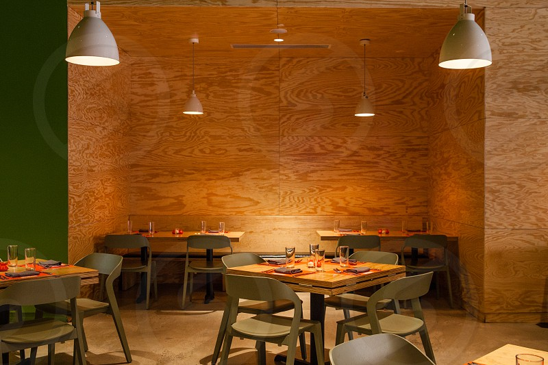brown wooden table sets on restaurant below grey ceiling 4 lights during daytime photo