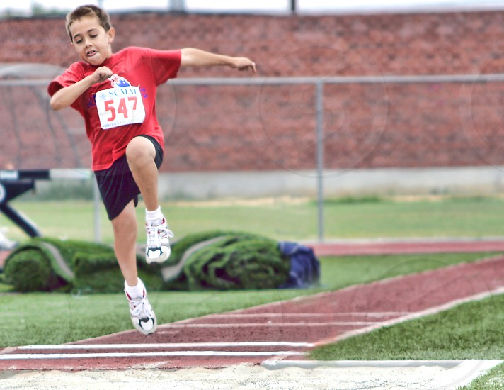 A little boy is caught in the air in a long jump event. photo