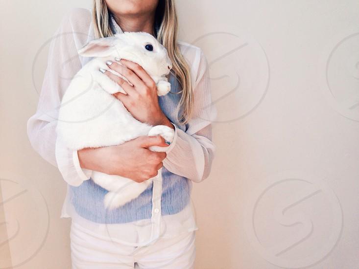 woman holding onto white rabbit photo