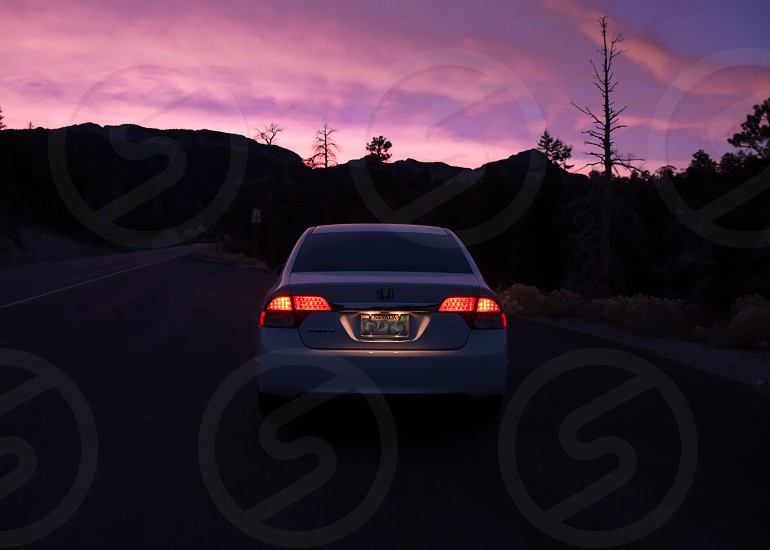 Photo take in Mount Charleston Nevada. Car tail lights in foreground with sunset and mountains in background. photo