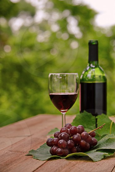 A bottle of red wine and fresh fruit outside fresh air photo