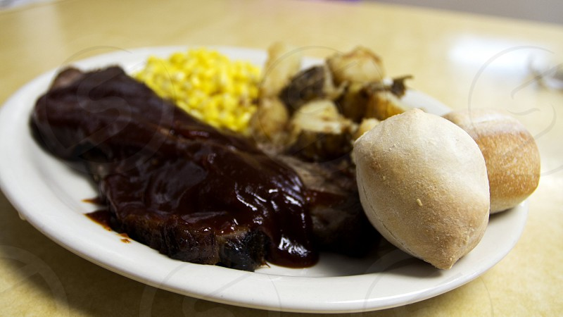 Barbecue brisket on plate with potatoes corn and roll white plate on beige tabletop photo