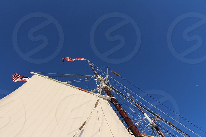 low-angle photography of red flag under blue sky during daytime photo