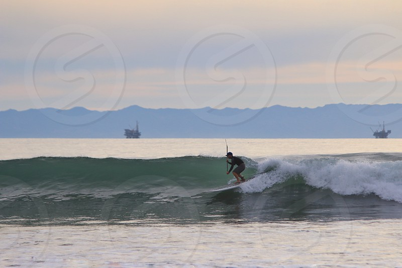 person surfboarding on sea during daytime photo
