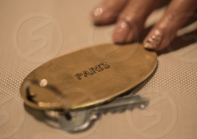 Hand of woman with key of luxury hotel room in France in Paris photo