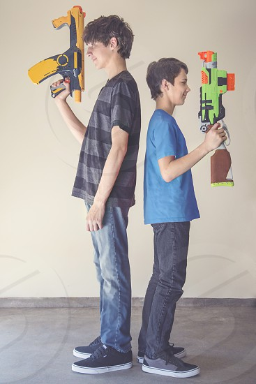 boy in gray and black stripe crew neck t-shirt holding yellow and black plastic toy gun standing back to back with boy in blue crew neck t-shirt holding green orange and brown plastic toy gun photo