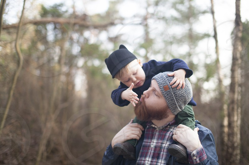 Dad hiking with son on his shoulders photo
