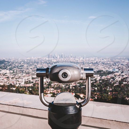 black and silver telescope facing the city in tilt shift lens photo