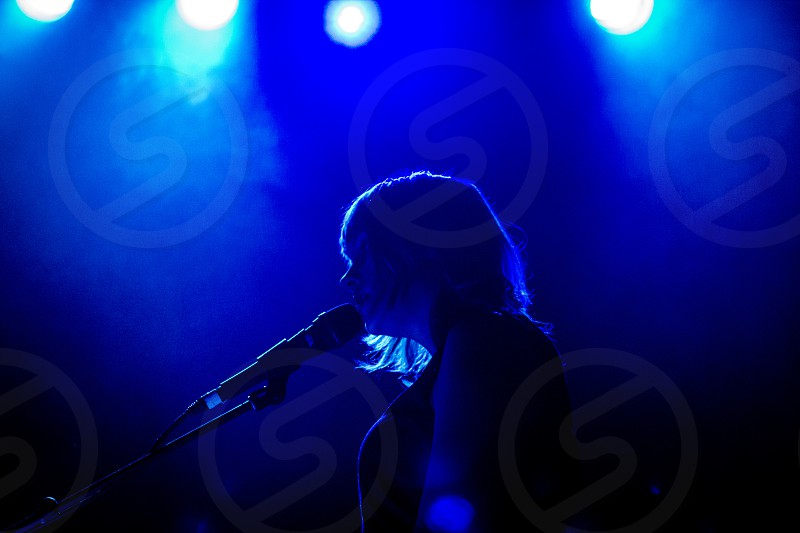 Female musician silhouette against a blue lit background while singing. photo