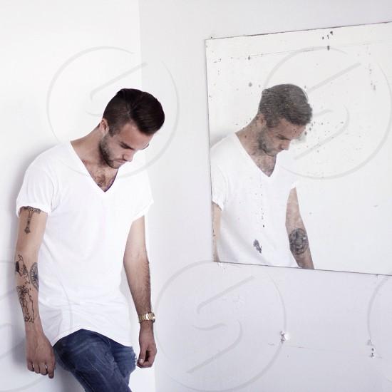 man wearing white v neck shirt and blue denim jeans photo