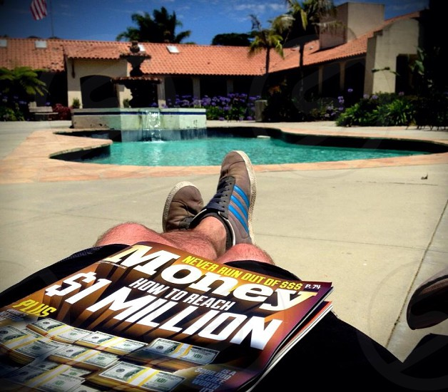 MOney magazine on the lap a person sitting poolside photo