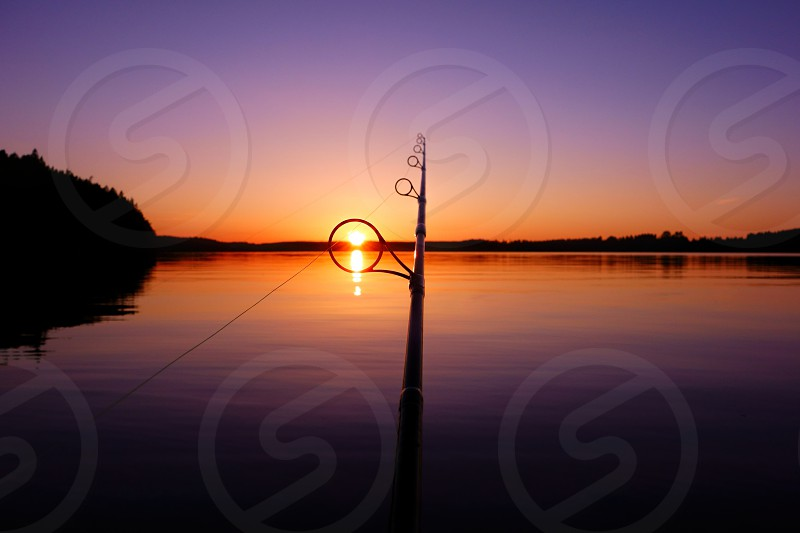 Sunset on a lake in Finland seen through a fishing rod ring on a warm and serene summer evening. photo