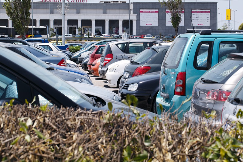 THESSALONIKI GREECE - AUGUST 1 2013: View over a hedge of tightly packed cars parked in an open-air car park in the sunshine in front of a commercial building photo