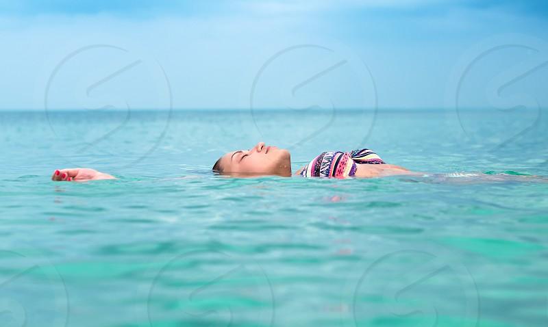 Young women lay in water in open ocean photo