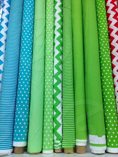 Fabric rolls textiles green blue red spots stripes zigzag colors row photo