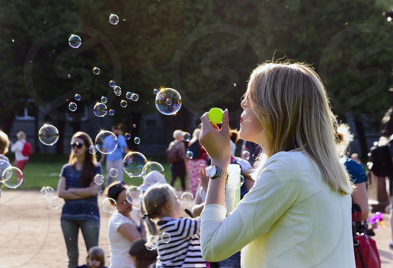 Beautiful woman in the park blowing soapbubbles photo