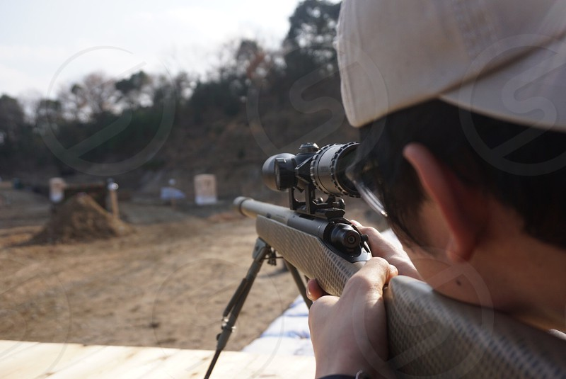 a close up photography of person wearing trucker cap with brown black sniper rifle aiming for a target inside the firing range during daytime photo