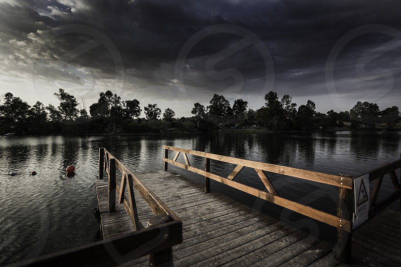 Pier with wooden balustrade illuminated by the sunset sun and sky covered with clouds photo