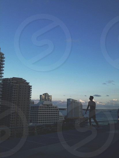 silhouette of man in walking gesture under blue sky photo