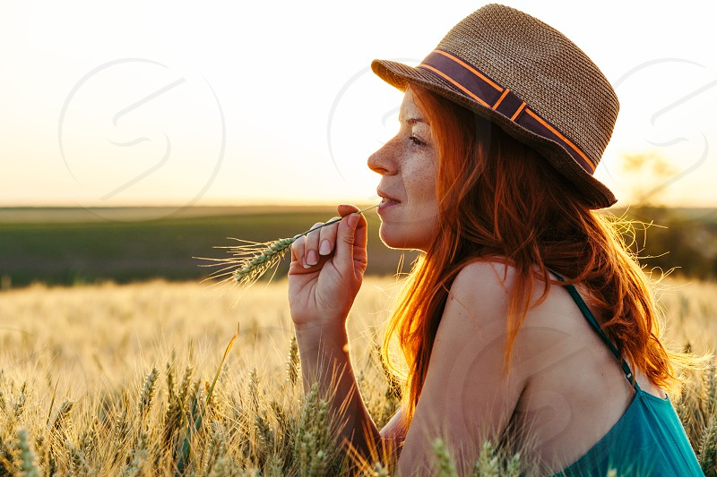 Young woman in the wheat field at the sunset photo