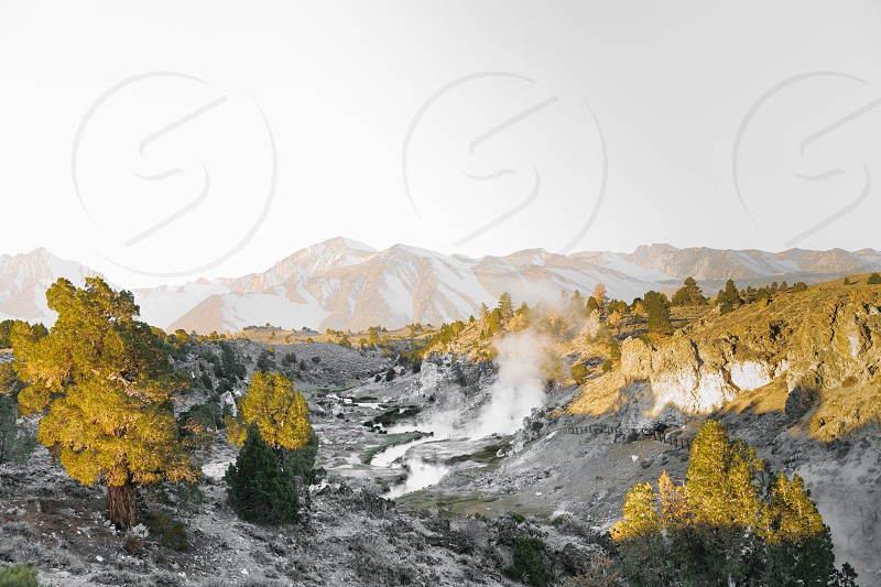 hot springs steaming through rugged rocks with mountains in the distance photo