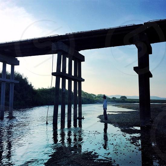 woman standing under brown wooden footbridge photo