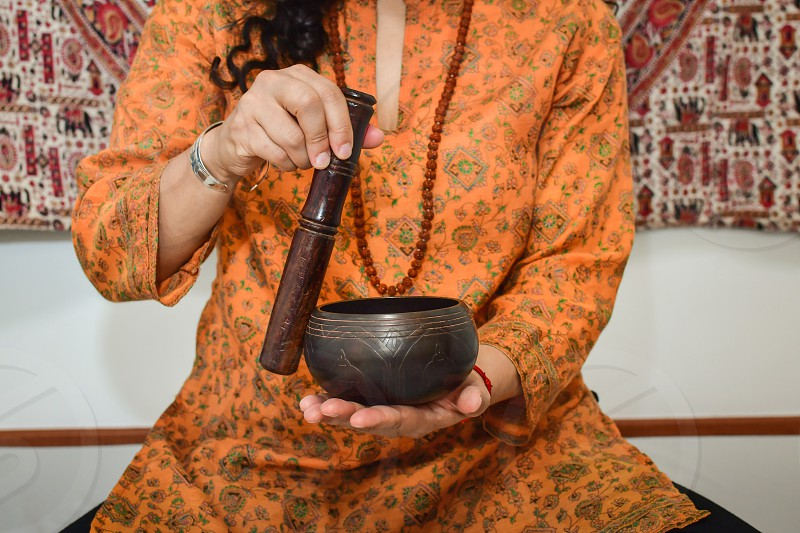 A woman practicing meditation and  healing with tibetan singing bowl. photo