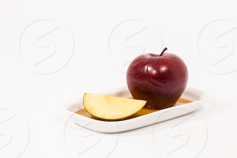 Red apple and red apple slice on white plate with honey isolated on a white background. Symbols of Jewish New Year - Rosh Hashanah.   photo