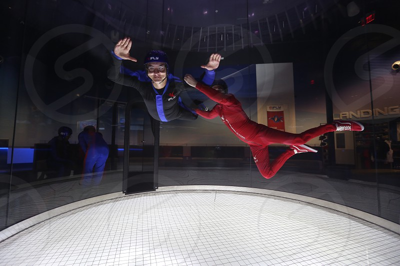 man wearing black suit while the other person wearing red suit holding the man hands and foot while on air photo