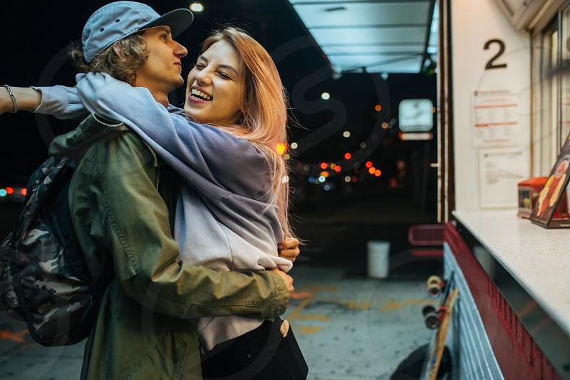 Young teenage couple hugging near ice cream shop at night photo